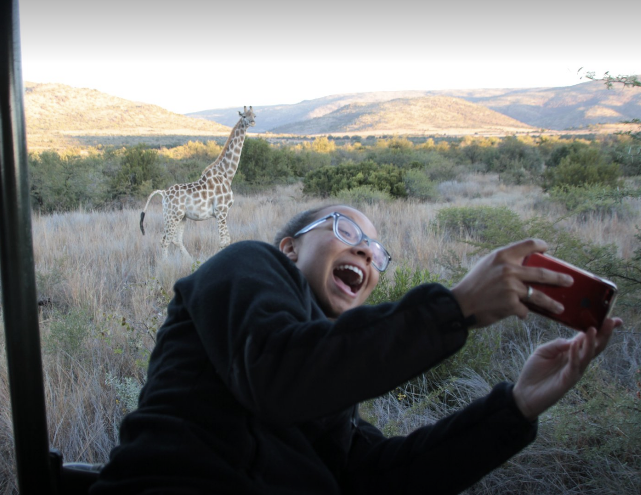 student taking picture with giraffe