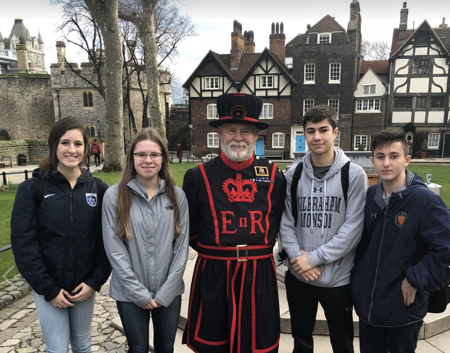 Students in England standing with a Beefeater