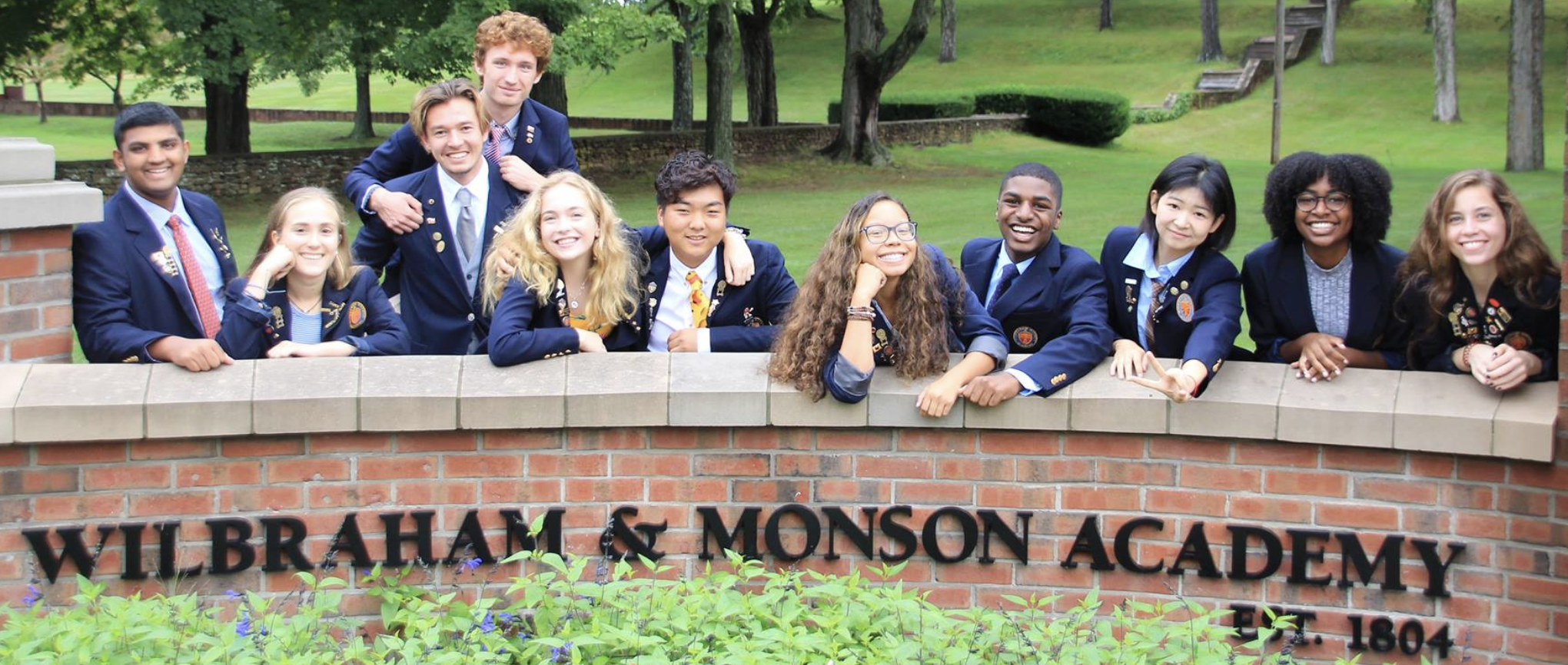 students in front of entrance sign